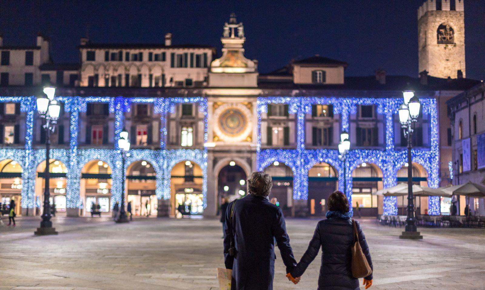 Coppia che passeggia in Piazza Loggia con luci di Natale
