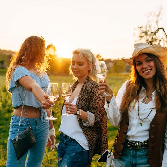 tre amiche in un tour tra le vigne al tramonto