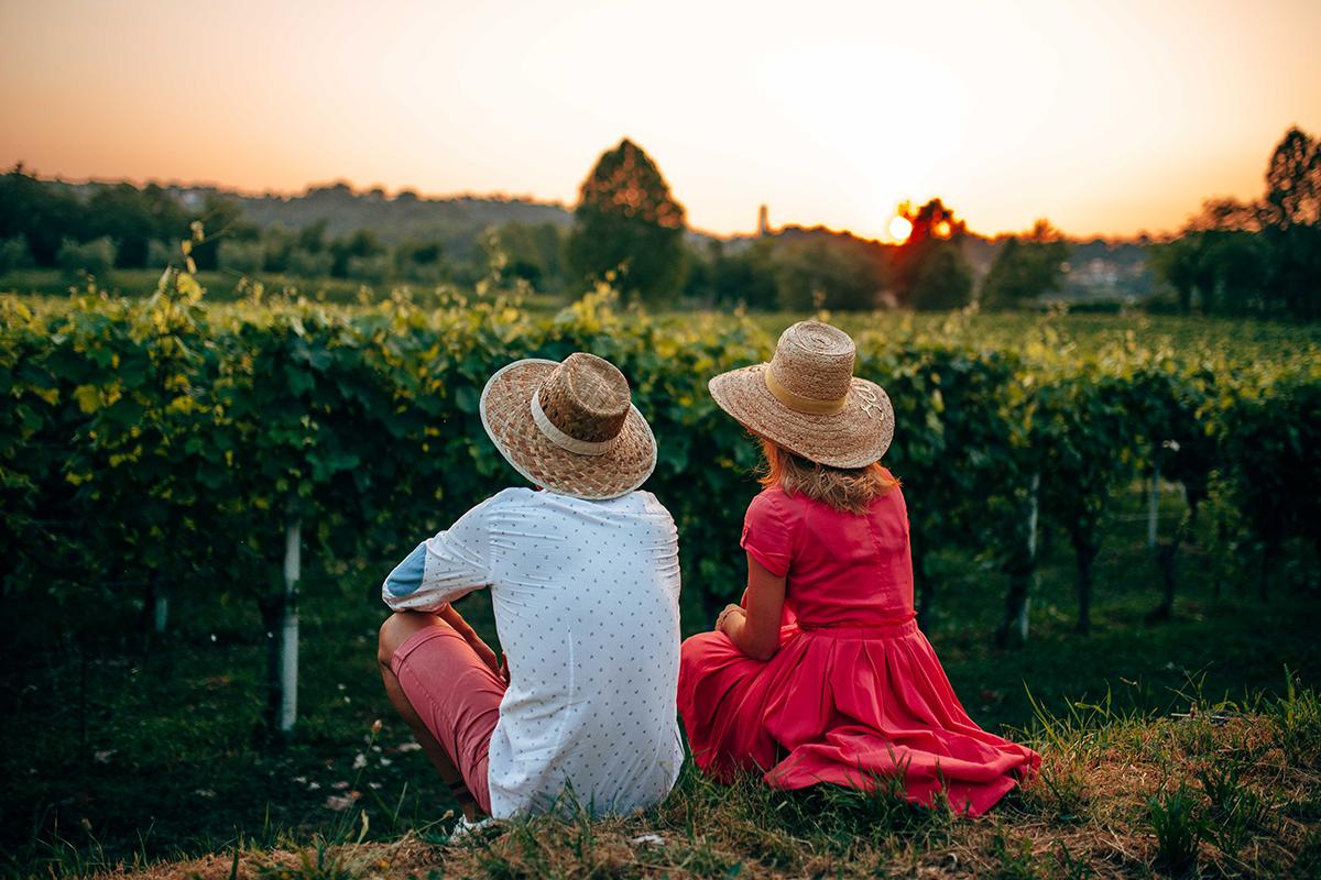 coppia seduta davanti al vigneto al tramonto